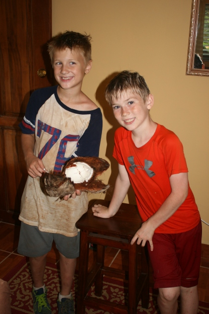 Owen and Jacob, cracking a coconut open.  and then rolling in the mud.   Literally...